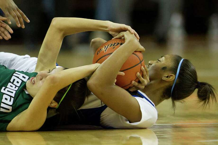 Spring Dekaney forward Shunta Nevitt (30) wrestles with San Antonio Reagan guard Tessa Ramiriz (20) for a loose ball during first half action in a class 5A semifinal game during the UIL girls state basketball tournament at the Frank Erwin Center on Friday, March 2, 2012, in Austin. Photo: Smiley N. Pool, Houston Chronicle / © 2012  Houston Chronicle