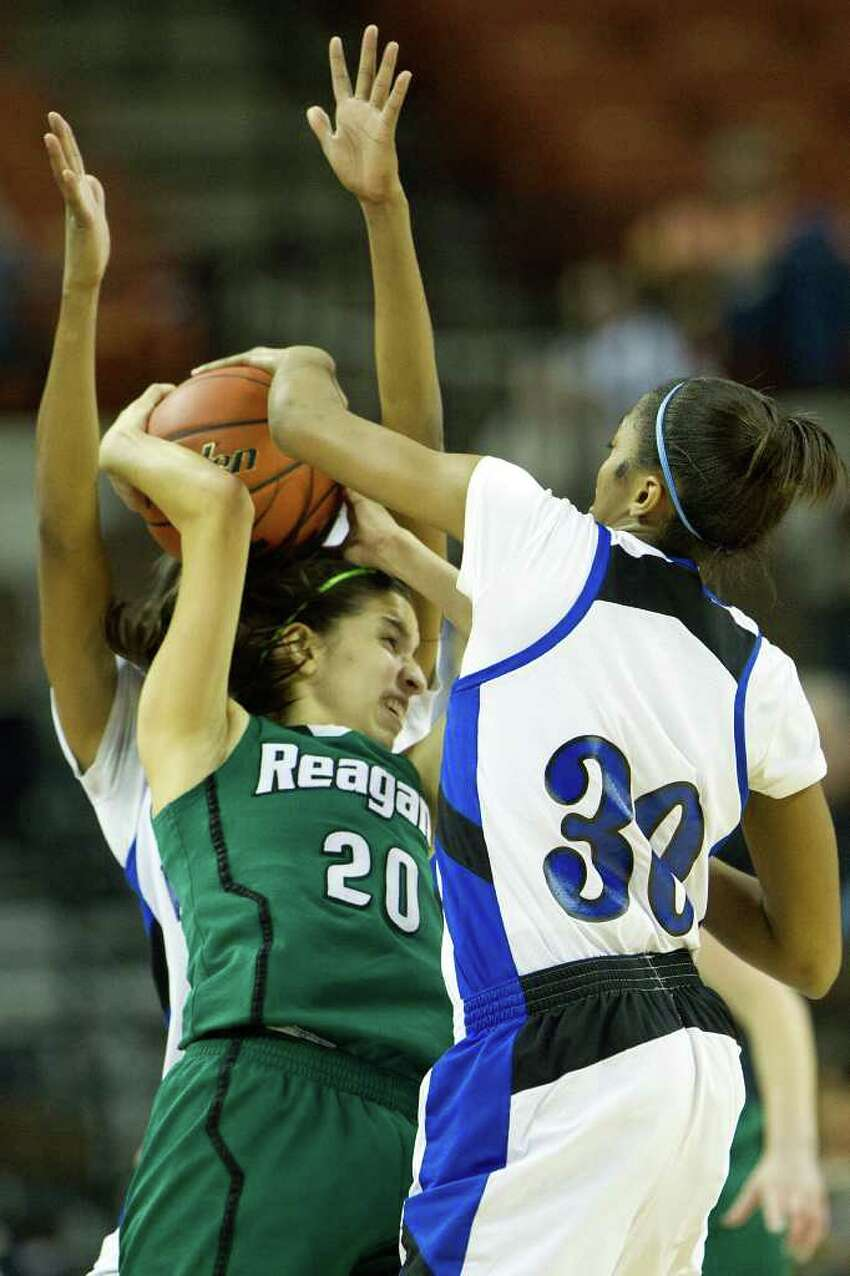 San Antonio Reagan guard Tessa Ramiriz (20) is sandwiched by the defense of Spring Dekaney forward Shunta Nevitt (30) and guard Jaleesa Chapel during first half action in a class 5A semifinal game during the UIL girls state basketball tournament at the Frank Erwin Center on Friday, March 2, 2012, in Austin.