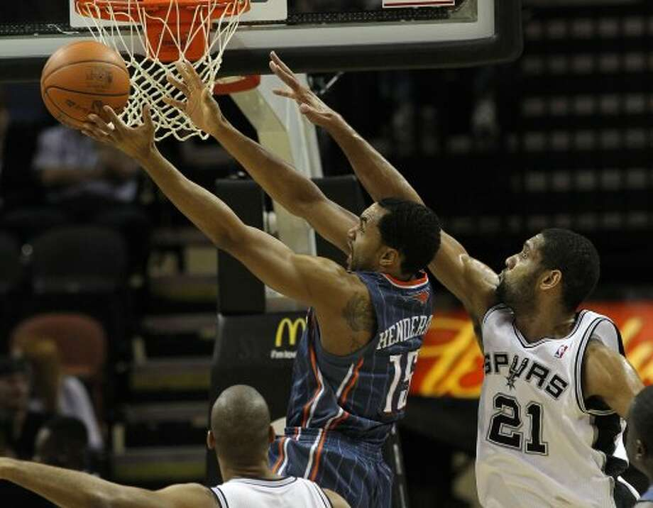 Spurs' Tim Duncan (21) attempts to block Charlotte Bobcats' Gerald Henderson (15) in the first half at the AT&T Center on Friday, Mar. 2, 2012. Kin Man Hui/San Antonio Express-News (San Antonio Express-News)