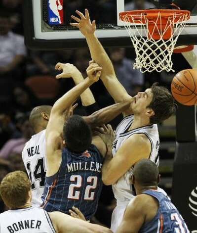 Spurs' Tiago Splitter (22) gets hits by teammate Gary Neal (14) while defending Charlotte Bobcats' Byron Mullens (22) in the first half at the AT&T Center on Friday, Mar. 2, 2012. Kin Man Hui/San Antonio Express-News (San Antonio Express-News)