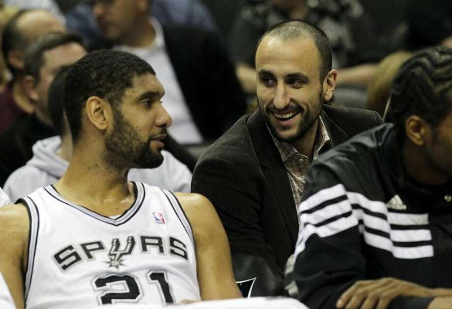 Spurs' Manu Ginobili (center) smiles while chatting with Tim Duncan (21) during their game against the Charlotte Bobcats at the AT&T Center on Friday, Mar. 2, 2012. Kin Man Hui/San Antonio Express-News (San Antonio Express-News)