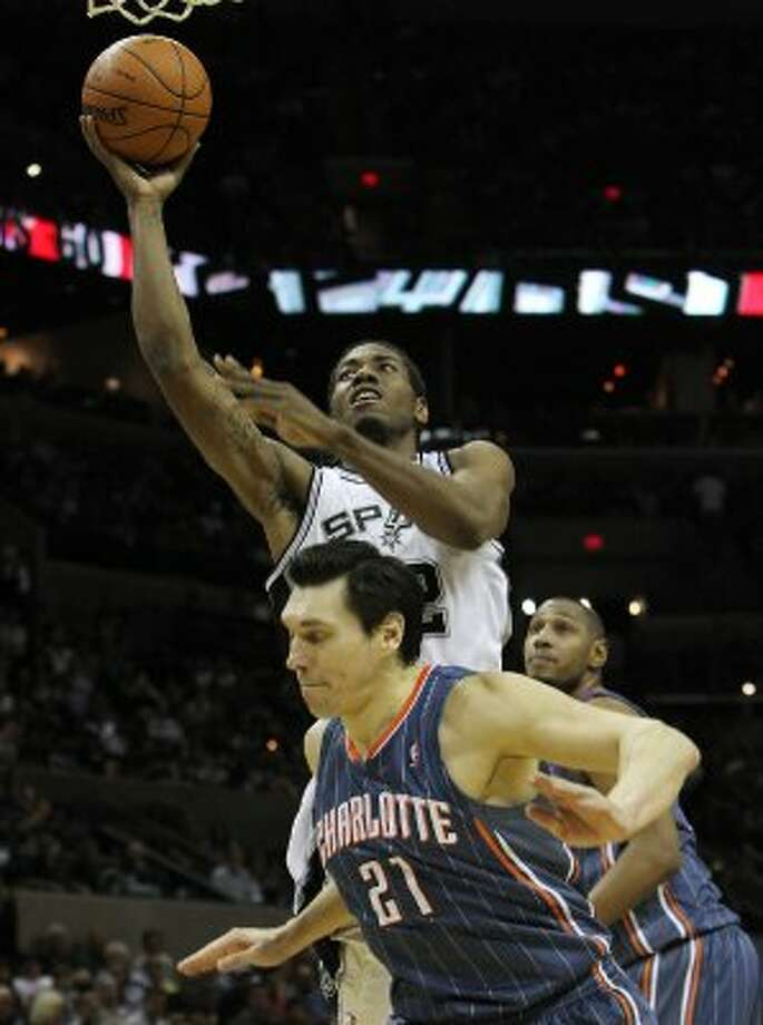 Spurs' Kawhi Leonard (02) goes up for a shot against Charlotte Bobcats' Eduardo Najera (21) in the second half at the AT&T Center on Friday, Mar. 2, 2012. Kin Man Hui/San Antonio Express-News (San Antonio Express-News)