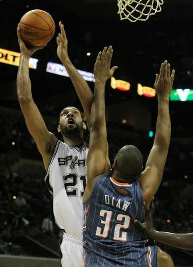 Spurs' Tim Duncan (21) shoots against Charlotte Bobcats' Boris Diaw (32) in the second half at the AT&T Center on Friday, Mar. 2, 2012. Kin Man Hui/San Antonio Express-News (San Antonio Express-News)