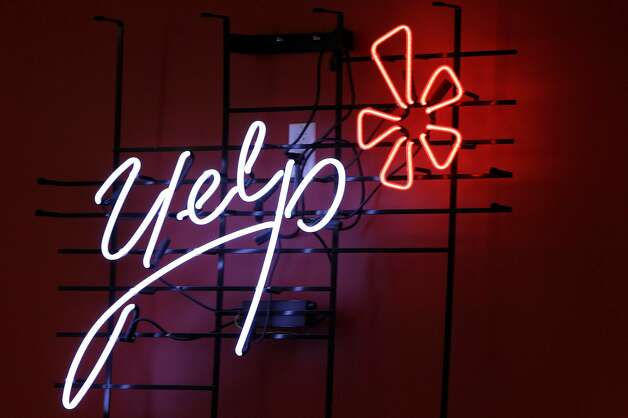 FILE - In this Oct. 26, 2011 file photo, the logo of the online reviews website Yelp is shown in neon on a wall at the company's new Manhattan offices in New York. Online reviews site Yelp is expected to price its initial public offering of stock on Thursday , March 1, 2012, and become the latest in a long line of social websites going public.  (AP Photo/Kathy Willens, File) Photo: Kathy Willens, Associated Press