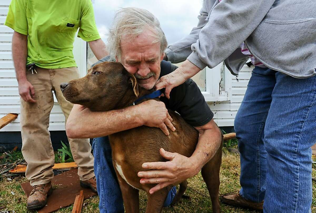 Greg Cook hugs his dog Coco after finding her inside his destroyed home in the East Limestone, Ala. on Friday, March 2, 2012. A reported tornado destroyed several houses in northern Alabama as storms threatened more twisters across the region Friday (AP Photo/The Decatur Daily, Gary Cosby Jr.)