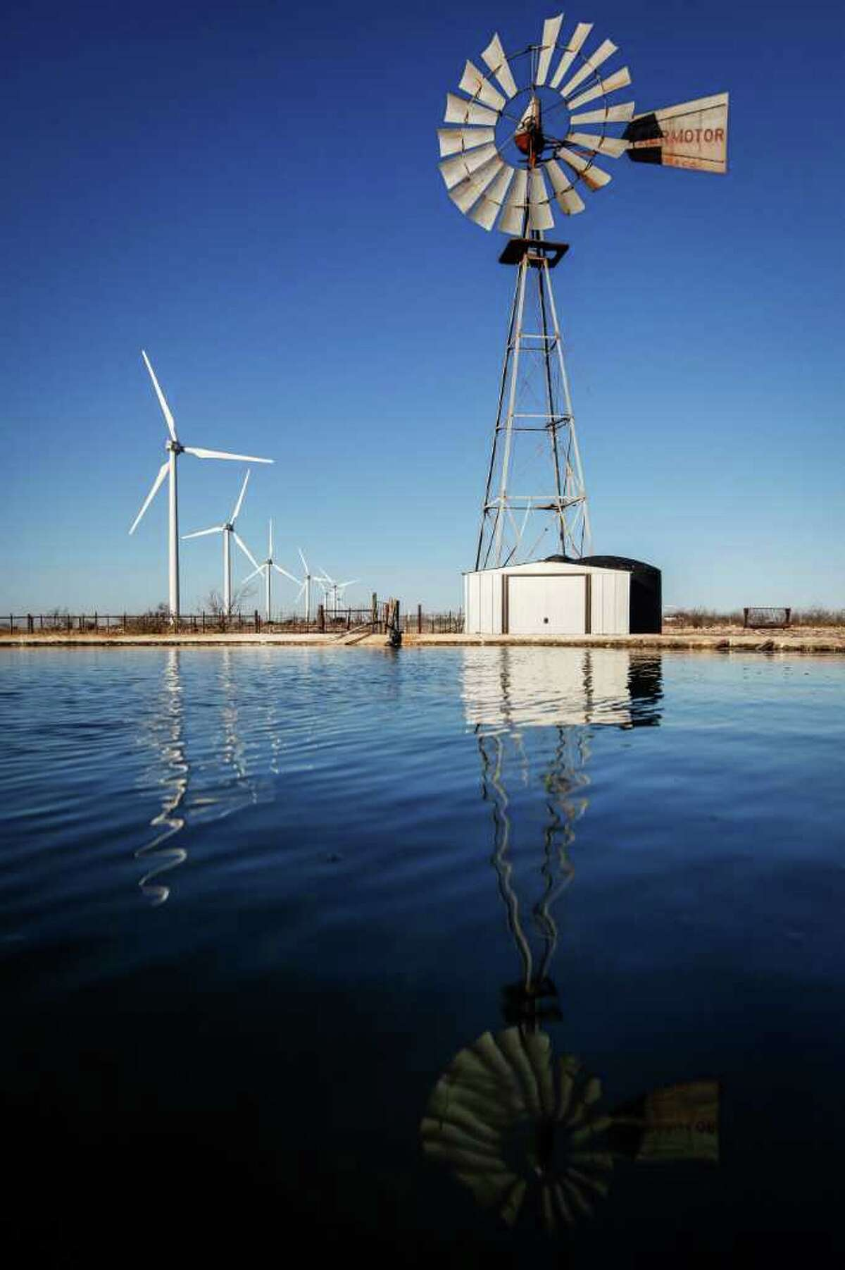 An old windmill is situated near several wind turbines at BP's Sherbino 2 wind farm near Fort Stockton.