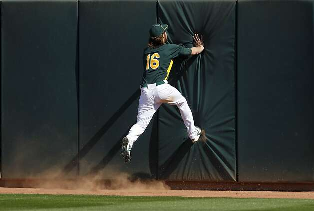 Right fielder Josh Reddick runs out of room trying to chase down Luis Rodriguez's 5th inning homer  in the Oakland A's Cactus League spring training opener against the Seattle Mariners in Phoenix, Ariz. on Friday, March 2, 2012. Photo: Paul Chinn, The Chronicle