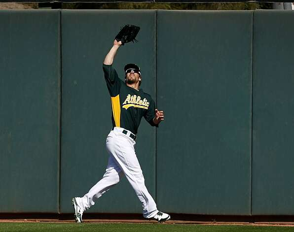 Center fielder Collin Cowgill fights off the sun while fielding a fly in the A's Cactus League spring training opener against the Seattle Mariners in Phoenix, Ariz. on Friday, March 2, 2012. Photo: Paul Chinn, The Chronicle