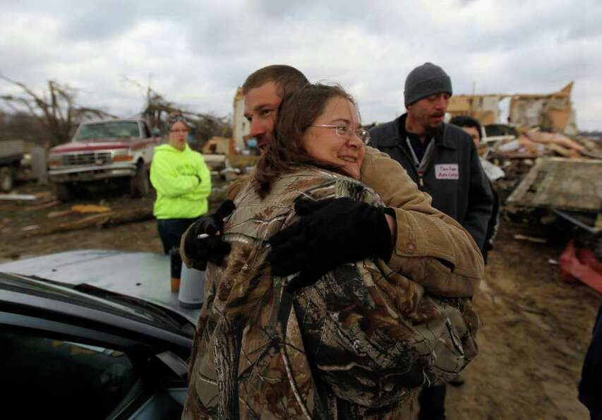 HOLTON, IN - MARCH 03:  Frank McRoberts hugs his aunt Vickie Patrick in front of her home that was d