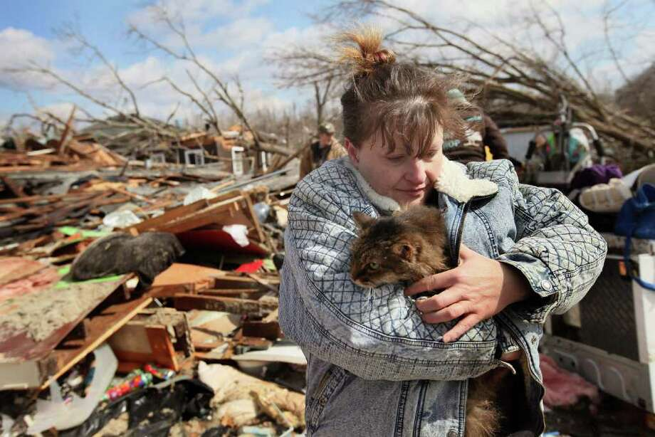 HENRYVILLE, IN - MARCH 03:  Melody Zollman hugs her cat Thumbelina after it was pulled from the debris of her home, which was destroyed by a tornado March 3, 2012 in Henryville, Indiana. Dozens of people were killed as severe weather and tornados ripped through the South and Midwest yesterday.  (Photo by Scott Olson/Getty Images) Photo: Scott Olson, Getty Images / 2012 Getty Images