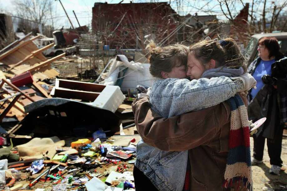 HENRYVILLE, IN - MARCH 03:  Melody Zollman (L) gets a hug from her sister Michelle Browning as they stand in what was Zollman's home after it was destroyed by a tornado March 3, 2012 in Henryville, Indiana. Dozens of people were killed as severe weather and tornados ripped through the South and Midwest yesterday.  (Photo by Scott Olson/Getty Images) Photo: Scott Olson, Getty Images / 2012 Getty Images