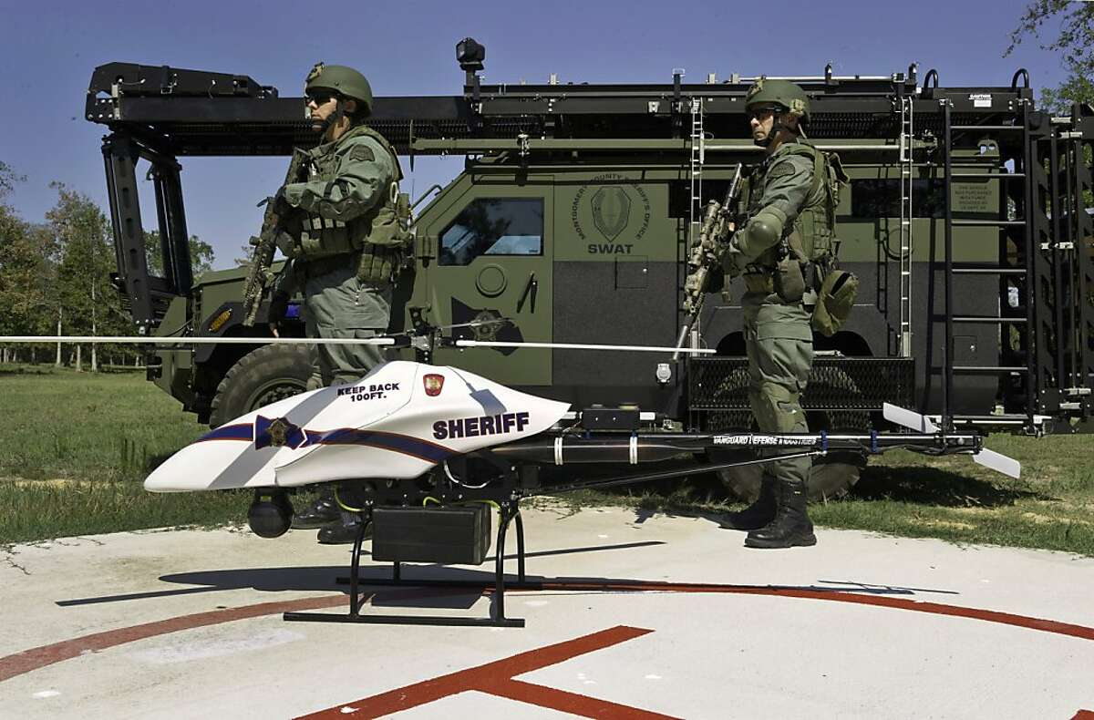 ADVANCE FOR MONDAY, FEB. 27, 2012 AND THEREAFTER - This Sept. 2011 photo provided by Vanguard Defense Industries, shows a ShadowHawk drone with Montgomery County, Texas SWAT team members. Unmanned military aircraft have tracked and killed terrorists in the Middle East and Asia. Their civilian cousins are now in demand by police departments, border patrols, power companies, news organizations and others wanting a bird's-eye view that's too impractical or dangerous for conventional planes or helicopters to get. Along with the enthusiasm, there are qualms. Drones overhead could invade people's privacy. The government worries they could collide with passenger planes or come crashing down to the ground, concerns that have slowed more widespread adoption of the technology. (AP Photo/Lance Bertolino, Vanguard Defense Industries)