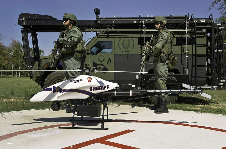 ADVANCE FOR MONDAY, FEB. 27, 2012 AND THEREAFTER - This Sept. 2011 photo provided by Vanguard Defense Industries, shows a ShadowHawk drone with Montgomery County, Texas SWAT team members. Unmanned military aircraft have tracked and killed terrorists in the Middle East and Asia. Their civilian cousins are now in demand by police departments, border patrols, power companies, news organizations and others wanting a bird's-eye view that's too impractical or dangerous for conventional planes or helicopters to get. Along with the enthusiasm, there are qualms. Drones overhead could invade people's privacy. The government worries they could collide with passenger planes or come crashing down to the ground, concerns that have slowed more widespread adoption of the technology. (AP Photo/Lance Bertolino, Vanguard Defense Industries) Photo: Lance Bertolino, Associated Press