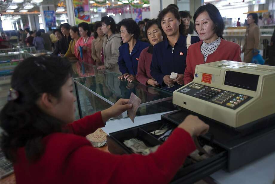 In this Sunday Oct. 9, 2011 photo, North Korean customers line up to pay for their purchases at Pyongyang Department Store No. 1 in downtown Pyongyang, North Korea. A new culture of commerce is springing up, with China as its inspiration and source. The new consumerism is part of a campaign launched three years ago to build up the economy, and so the image of new leader Kim Jong Un. (AP Photo/David Guttenfelder) PART OF A 34 PICTURE SERIES BY DAVID GUTTENFELDER Photo: David Guttenfelder, Associated Press