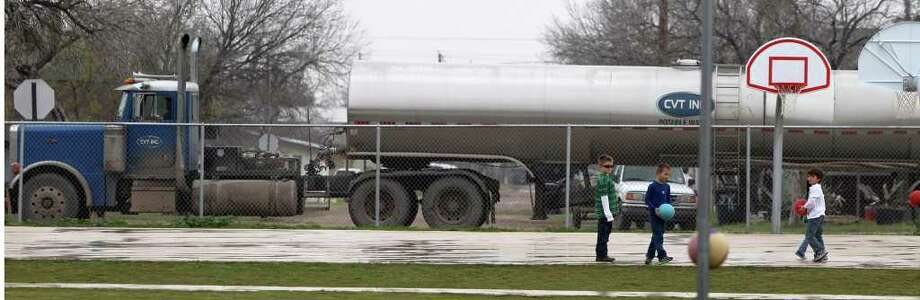 Students from McMullen County Elementary School in Tilden, Texas play ball Wednesday February 15, 2012 as a tanker truck passes by the school's playground. The McMullen County Independent School District is in the Eagle Ford shale formation area and enrollment in the district has seen an increase of 27 percent as people come looking for jobs related to the oil and gas industry. Truck traffic in the small town has also increased dramatically. Photo: SAN ANTONIO EXPRESS-NEWS