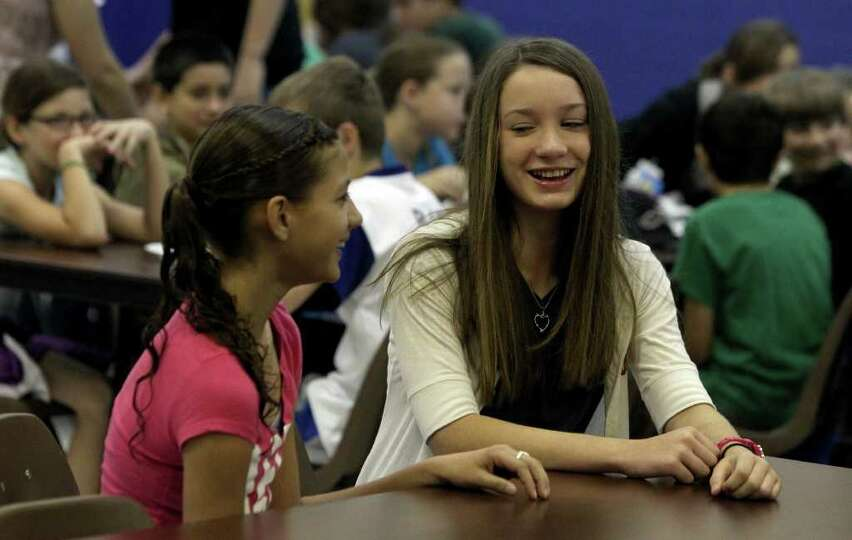 Courtney Cole,12, (right) chats with her friend Makinna Serrata,12, (left) in the cafeteria at schoo