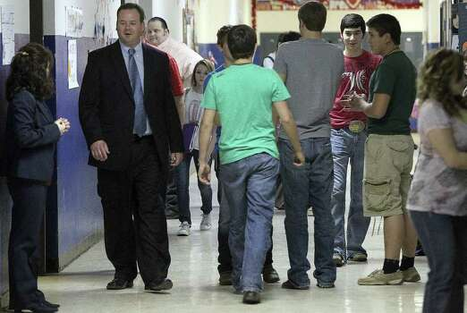 McMullen County Independent School District Superintendent Dave Underwood (left, wearing suit) walks the halls at the high school in Tilden, Texas where enrollment has been on the rise. Underwood has noticed changes in the the town as well as the school because of workers coming to the area to get jobs created by the Eagle Ford shale boom. John Davenport/San Antonio Express-News Photo: SAN ANTONIO EXPRESS-NEWS
