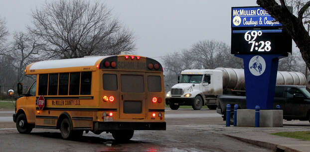 A McMullen County Independent School District bus leaves the school in Tilden, Texas Wednesday February 15, 2012 as a tanker truck passes by. Tilden is in the Eagle Ford shale area where drilling for oil and gas is on the rise. Enrollment at the small school district's schools is also on the rise as people come to the area seeking jobs. John Davenport/San Antonio Express-News Photo: JOHN DAVENPORT, SAN ANTONIO EXPRESS-NEWS / SAN ANTONIO EXPRESS-NEWS (Photo can be sold to the public)