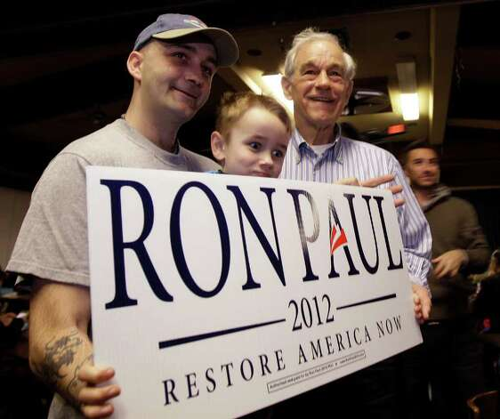 Republican presidential candidate Rep. Ron Paul, R-Texas, right, poses for a photo with supporter David Larsen, left, and his step-son Zac, during a Washington state caucus meeting Saturday in Puyallup. Photo: AP