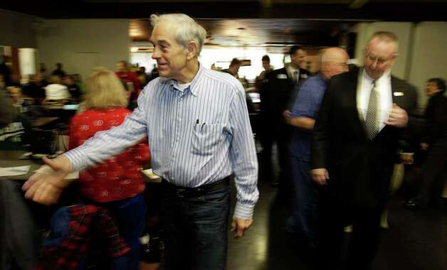 Republican presidential candidate Rep. Ron Paul, R-Texas, shakes hands as he greets voters taking part in Washington state caucus meetings Saturday in Puyallup.. Photo: AP