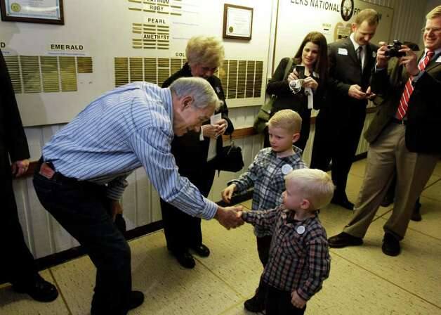 Republican presidential candidate Rep. Ron Paul, R-Texas, left, shakes hands with two young supporters as he and his wife Carol, center,  greets people taking part in Washington state caucus meetings Saturday in Puyallup. Photo: AP