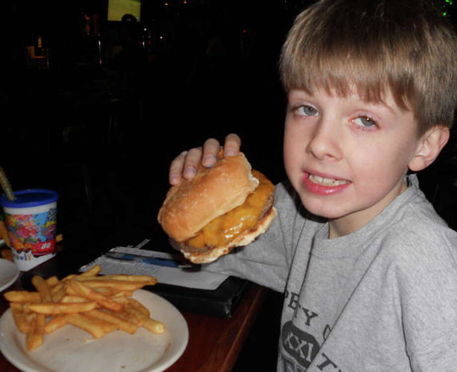 Will Siverson, 8, of Fairfield, 8, enjoys a cheddar cheeseburger at The Angus in Fairfield. Photo: Patti Woods / Fairfield Citizen contributed