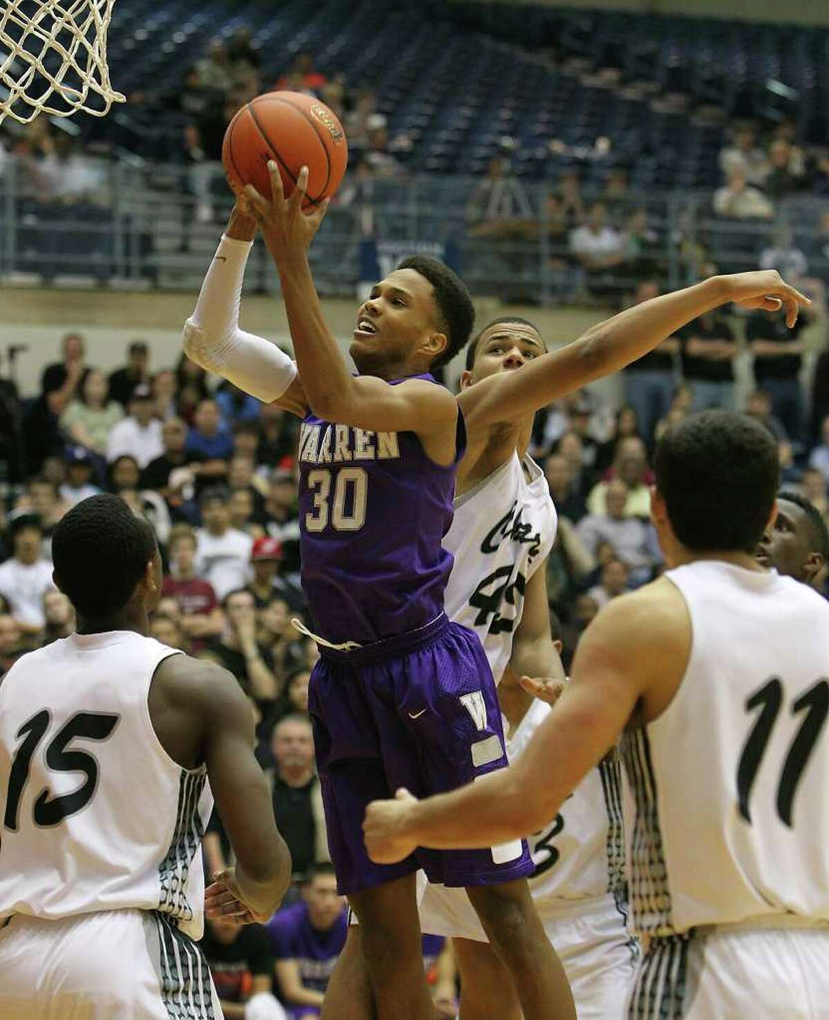 Warren's Jerell Ellis (30) grabs a rebound against Clark's Travis Matthews (15) and Shawn Gulley (45) in the Region IV-5A boys basketball finals at UTSA on Saturday, Mar. 3, 2012. Warren defeated Clark, 65-56, to earn a trip to the state tournament.
