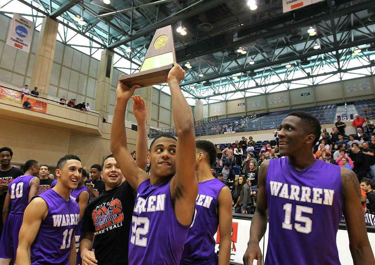 Warren's Jordan Corona (22) holds up the Region IV-5A trophy as teammates look on after the Warriors defeated the Clark Cougars in the Region IV-5A boys basketball finals at UTSA on Saturday, Mar. 3, 2012. Warren defeated Clark, 65-56, to earn a trip to the state tournament.
