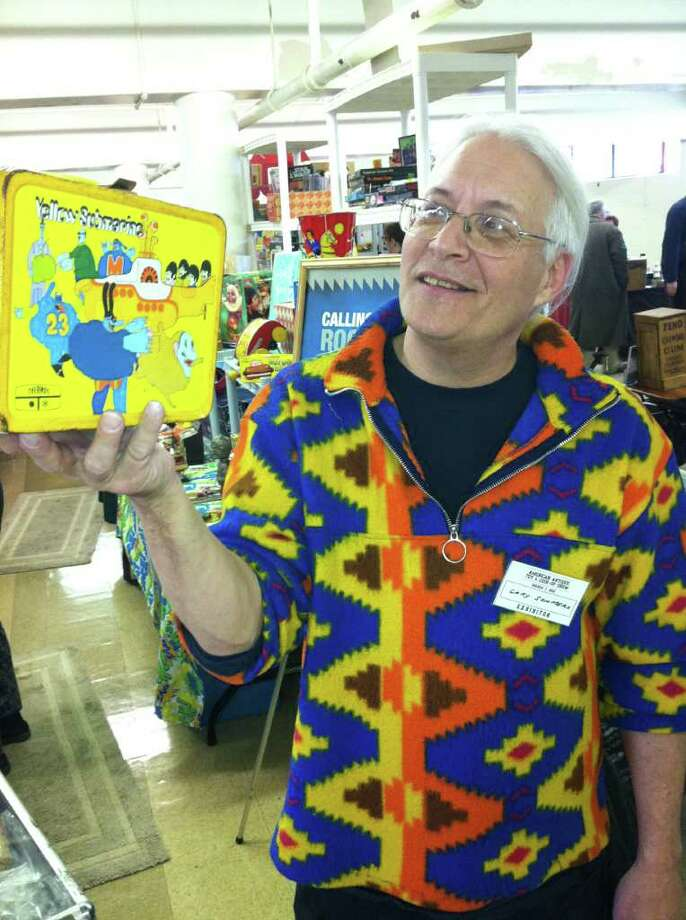 "Gary Sohmers, of Hudson, Mass., holds a lunch box decorated with the Beatles Yellow Submarine Saturday at an antique toys and coin-operated arcade machines show at the Eastern Greenwich Civic Center. Sohmers has appeared as an appraiser on the PBS television show ""Antiques Roadshow."" Photo: Frank MacEachern"