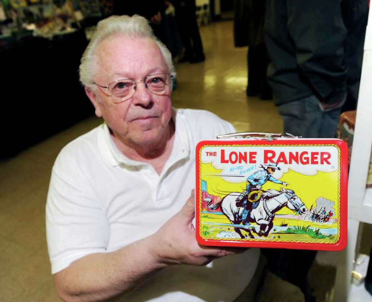 Joseph Soucy of Westerly, R.I., holds up a 1955 Lone Ranger lunch box that he was selling for $1,450 during the American antique toy and coin-op show at the Eastern Greenwich Civic Center, Saturday, March 3, 2012.