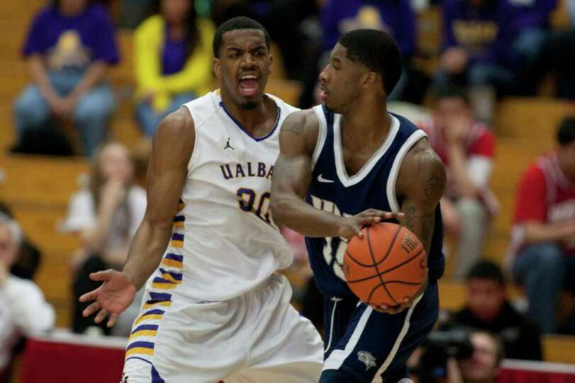 Jayson Guerrier of UAlbany hollers as he defends Ferg Myrick (right) of UNH, during the America East