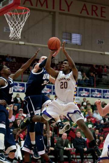 Gerardo Suero of UAlbany (right) scores 2 of his game high 24 points during the America East Confere