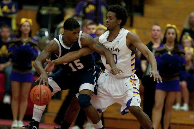 Gerardo Suero of UAlbany (right) gets his hand in on defense against Ferg Myrick of UNH, during the