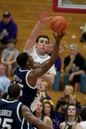 Sam Rowley of UAlbany (center) blocks a shot by Ferg Myrick of UNH, during the America East Conferen