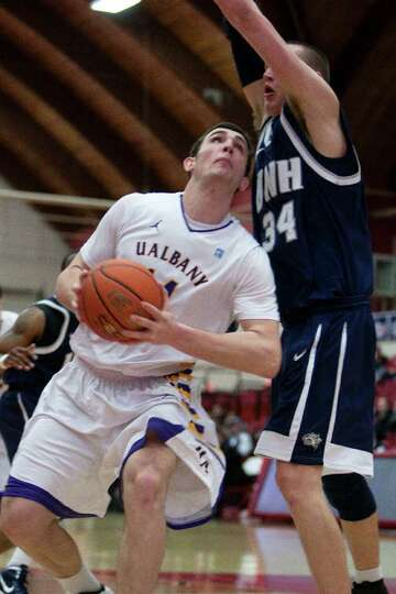 Sam Rowley of UAlbany (center) bangs down low with Brian Benson (34) of UNH, during the America East