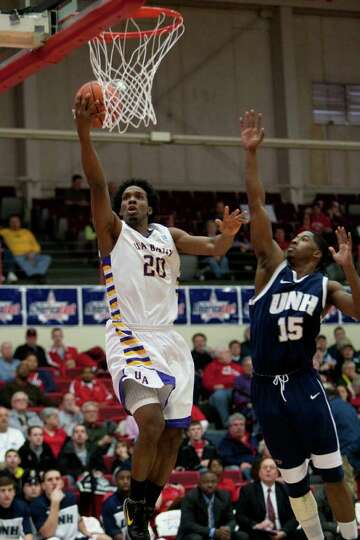 Gerardo Suero of UAlbany (left) gets separation and a layup against Ferg Myrick of UNH, during the A