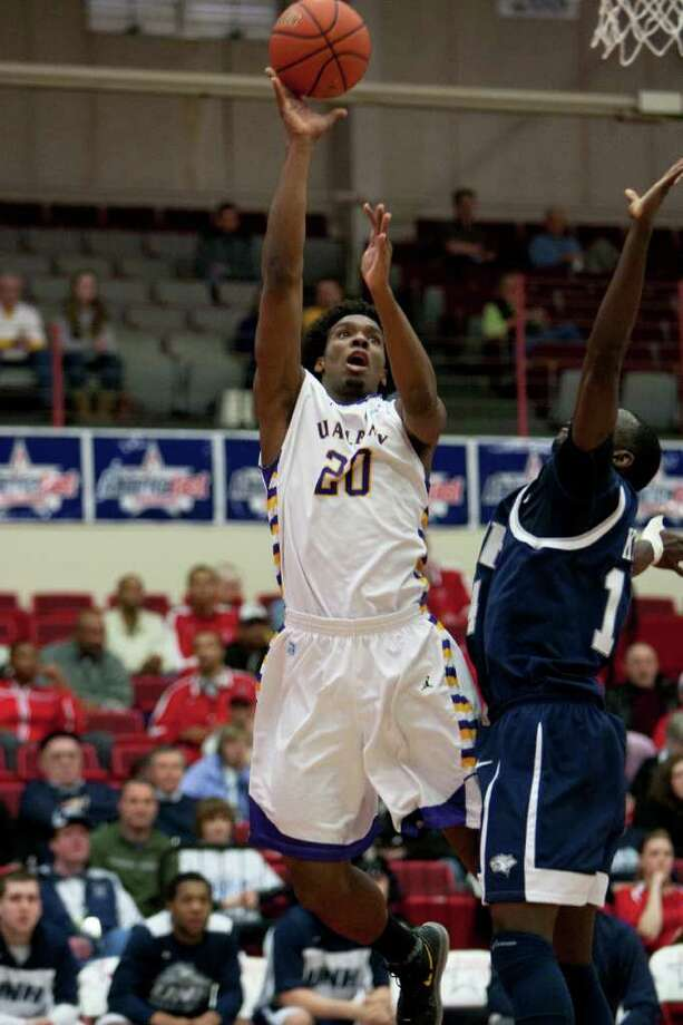 Gerardo Suero of UAlbany (right) puts in 2 of his game high 24 points against Patrick Konan of UNH, during the America East Conference Tournament Quarterfinal against the Wildcats at Chase Family Arena in Hartford, CT on March 3, 2012 (Shane Bufano/Special to the Times Union). Photo: Shane Bufano