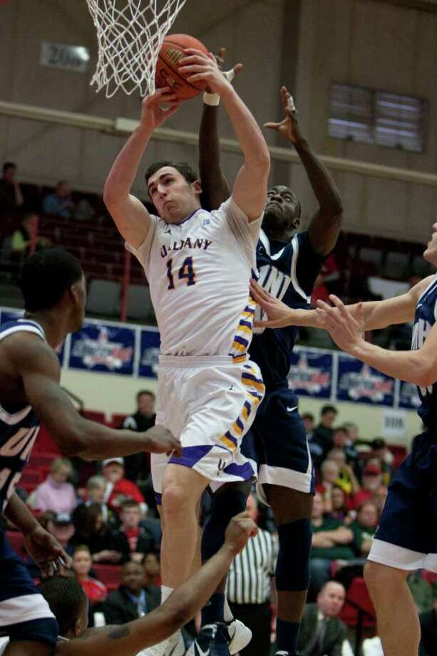 Sam Rowley of UAlbany (left) is fouled from behind by Patrick Konan of UNH, during the America East Conference Tournament Quarterfinal against the Wildcats at Chase Family Arena in Hartford, CT on March 3, 2012 (Shane Bufano/Special to the Times Union). Photo: Shane Bufano