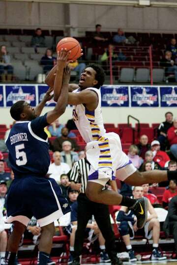Gerardo Suero of UAlbany (right) is fouled by Jordan Bronner of UNH going hard to the hoop, during t