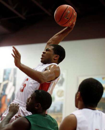 The Fort Bend Travis Tigers Andrew Harrison (5) shoots over Fort Bend Hightower for the 5A regional