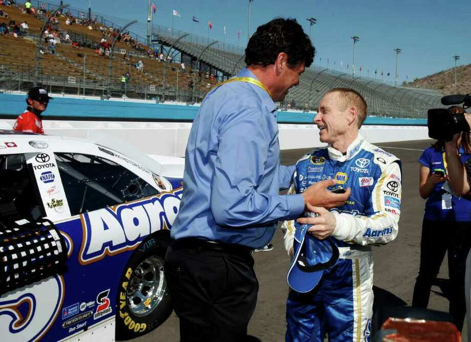 Mark Martin, right, talks with team owner Michael Waltrip, left, after winning the pole during qualifying for Sunday's NASCAR Sprint Cup Series auto race at Phoenix International Raceway, Saturday, March 3, 2012, in Avondale, Ariz. Photo: AP