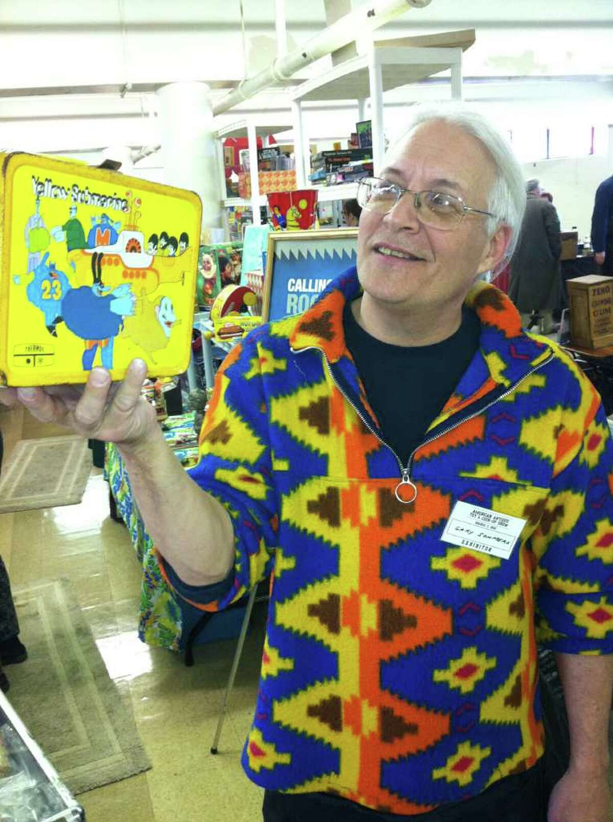"""Gary Sohmers, of Hudson, Mass., holds a lunch box decorated with the Beatles Yellow Submarine Saturday at an antique toys and coin-operated arcade machines show at the Eastern Greenwich Civic Center. Sohmers has appeared as an appraiser on the PBS television show """"Antiques Roadshow."""""""