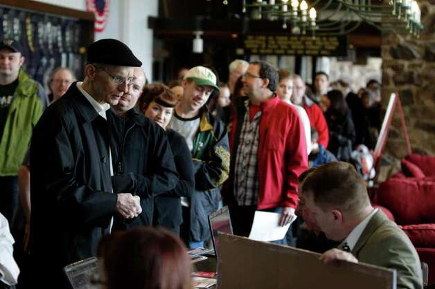 Voters line up to check in for a Washington state Republican caucus meeting Saturday in Puyallup. Photo: AP