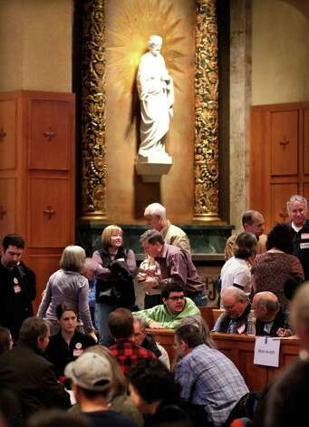 Republican caucus attendees talk near a religious statue at the former St. Edward Seminary chapel Saturday in Kenmore. Nearly 600 Republicans from 74 precincts crowded in the venue, now part of the Bastyr University campus. Republicans crowded homes, churches and town halls across the state Saturday for Washington's GOP presidential caucuses, the first meaningful party contests in recent memory. While the caucuses are a nonbinding contest, state Republicans say it could create momentum for the four candidates on their last stop before Super Tuesday, when voting takes place in 10 states. Photo: AP