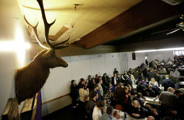 A mounted Elk head is shown as voters take part in discussions during a Washington state caucus meeting Saturday at an Elks Club in Puyallup. Thousands of Republican voters crowded schools, town halls and homes across the state Saturday for Washington's GOP presidential caucuses, the first meaningful party contests in the state in recent memory. Photo: AP
