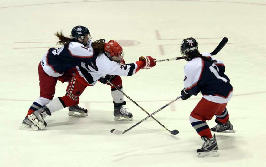 New Canaan's Olivia Hompe (22) takes a shot as West Hartford's Juliana Bailey-Simao (10) and Racheal Aronow (17) defend during the Connecticut High School Girls' Hockey Association Championship Game at Ingalls Rink in New Haven on Saturday, Mar. 3, 2012.