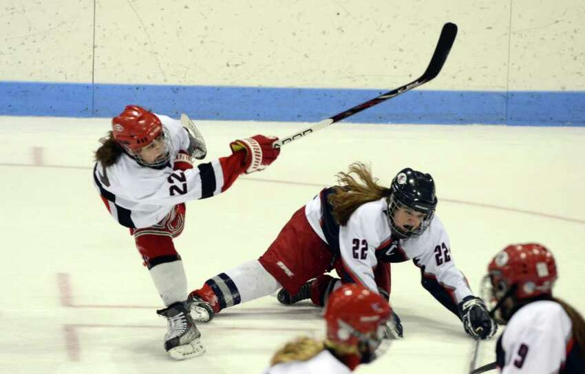 New Canaan's Olivia Hompe (22) takes a shot as West Hartford's Bailey Amenabar (22) falls to the ice during the Connecticut High School Girls' Hockey Association Championship Game at Ingalls Rink in New Haven on Saturday, Mar. 3, 2012.