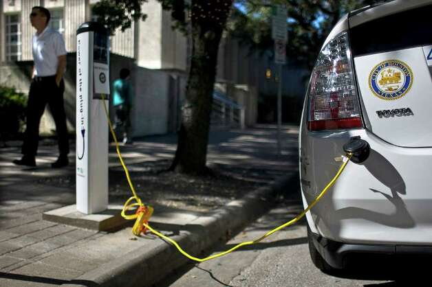 An electric vehicle charges outside City Hall in Houston. The city partnered with Reliant Energy to convert ten city-owned Toyota Priuses into plug-in hybrid electric vehicles. Photo: Johnny Hanson / Houston Chronicle