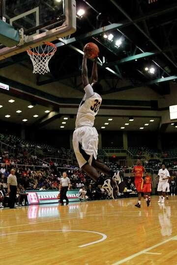 Jones' Broderick Harris, 30, slam dunks the ball during the first half of a 4A regional final high s