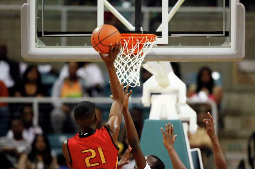 Yates' Damion Dotson, 21, puts up a floater, during the first half of a 4A regional final high schoo